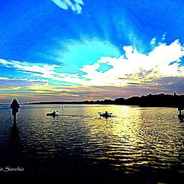 Kayakers paddling out to the watch the sunset near the pier in Safety Harbor, FL.