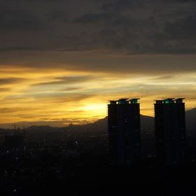 Towering condominiums and hill ranges reaching into the sunset over Kuala Lumpur