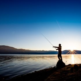 Fishing. Man is holding a fisher rod, standing on a rock over the water of the Dospat lake early in the morning, during the sunrise. Part of the ...