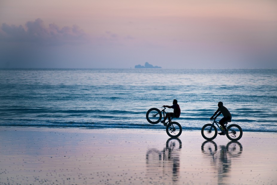 Bicycles on a beach in Thailand. In the background is Phi Phi island.