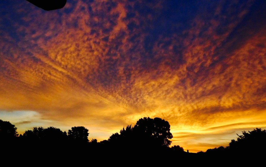 Sunrise on a cloud-filled late summer sky. The photo was taken from my living room window with a ...