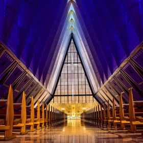 US Air Force Academy Cadet Chuch Interior from the grand entrance view at sunset with dim lights in the area for interesting color effect from th...