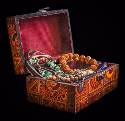 Old wooden open chest with jewelry on black background.