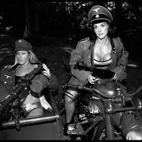 Two fitness models wearing old German military clothing, posing on a Zundap military motorcycle with sidecar, machine gun, Mauser.