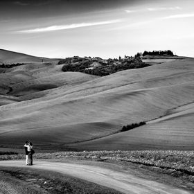 Couple kissing each other on a dusty path somewhere in Tuscany, Italy. The fields surrounding them are plowed. Black and white landscape with hum...