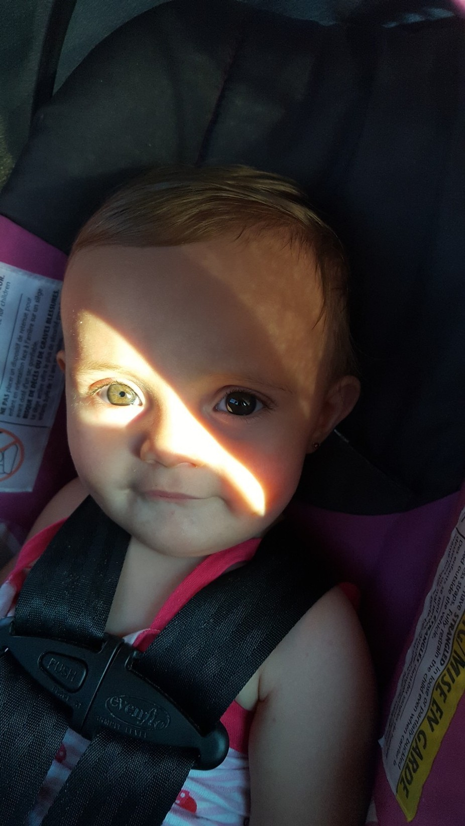 She was sitting in her car seat with the sun shinning in her eye