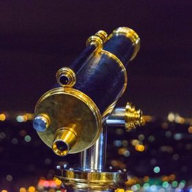 The Eiffel Tower at night is a magical place. This is one of the telescopes you can use and the second level. The lights in the city took on a bo...