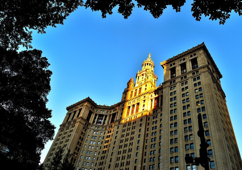 The sun sets on City Hall in Manhattan New York. The sun crowns the top of the building while the...
