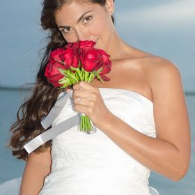 The bride/model takes a break from the photo session to smell the roses during Isla Pasion's latest advertising campaign