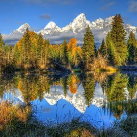 The Grand Tetons reflect into Schwabachers Landing on a majestic September morning as the clouds from a storm the night before pass along the pea...