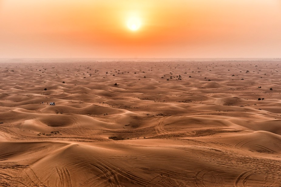 Looking over the desert while the sunsets, whilst 4x4s drive over the dunes