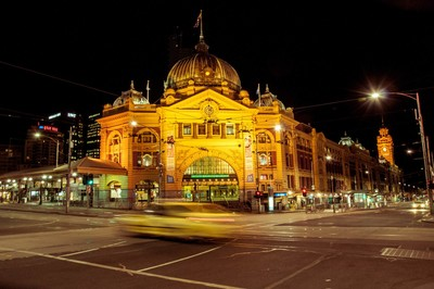 A yellow taxis speeds past Flinders Street Station, Melbourne, Australia