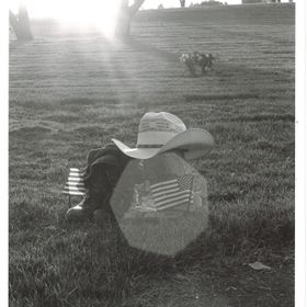 Backlit shot of Riverside National Cemetery with a pair of combat boots, boonie hat, cowboy boots and hat, accompanied by a set of miniature Amer...