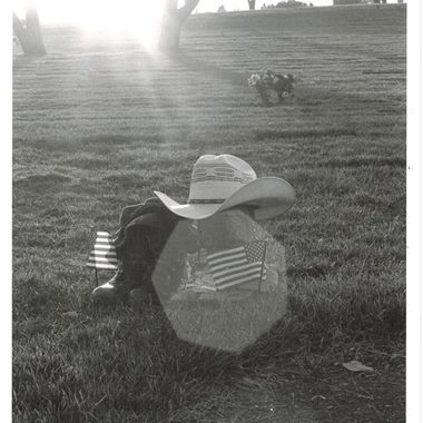 Backlit shot of Riverside National Cemetery with a pair of combat boots, boonie hat, cowboy boots and hat, accompanied by a set of miniature American flags. This was a shot I originally took for a representation of myself, in a place where my grandfather is buried. I absolutely love backlit photos like this with prism effects in them.  Many of my photos are for sale, please click over to my photography store and take a peek. I have something for just about anyone who loves nature.