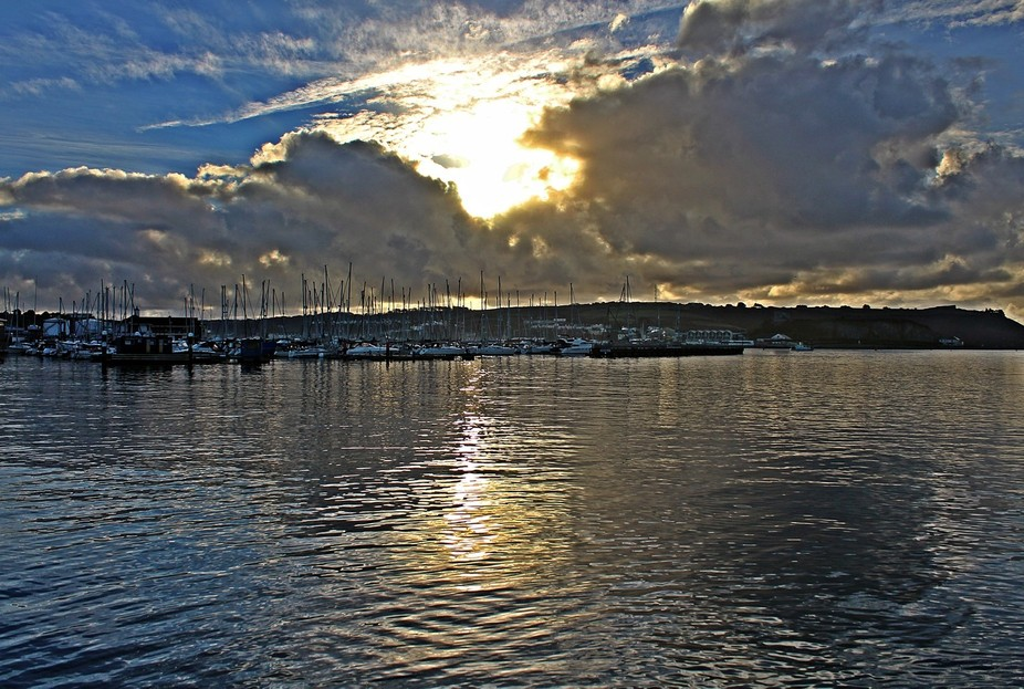 The sun breaks the clouds over Sutton Harbour in Plymouth Sound
