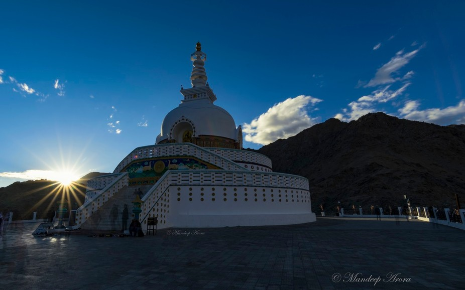 Beautiful sunset at Shanti Stupa which is a Buddhist white-domed stupa (chorten) on a hilltop in ...