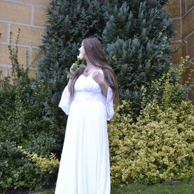 beautiful woman in wedding dress standing with rose in the garden