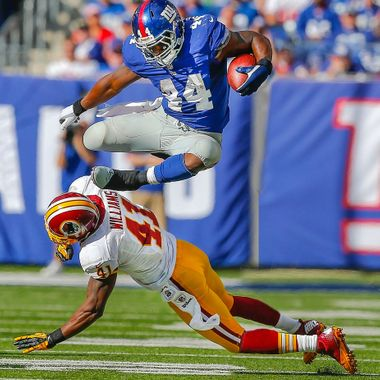 Oct 21, 2012; East Rutherford, NJ, USA;  New York Giants running back Ahmad Bradshaw (44) leaps over Washington Redskins free safety Madieu Williams (41) during the second half at MetLife Stadium. New York Giants defeat the Washington Redskins 27-23.