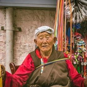 Tibet, candid shot of an old man sitting beside the street shop (Lhasa, Chin