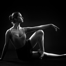 Ballerina sitting in an elegant pose. Black and white photo.