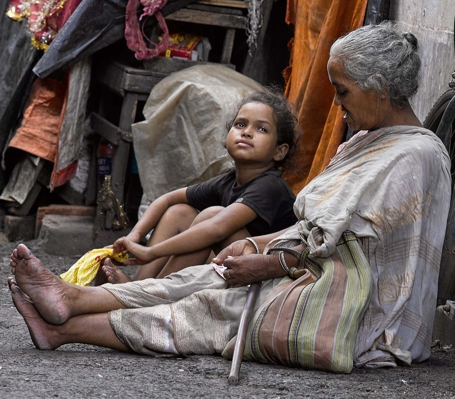 A toddler sits on the backstreets of Kolkata beside her grandmother, who is a lame beggar. Granny...