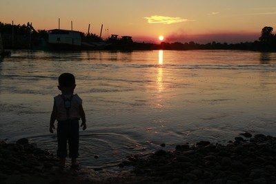The boy at riverbank with sunset.