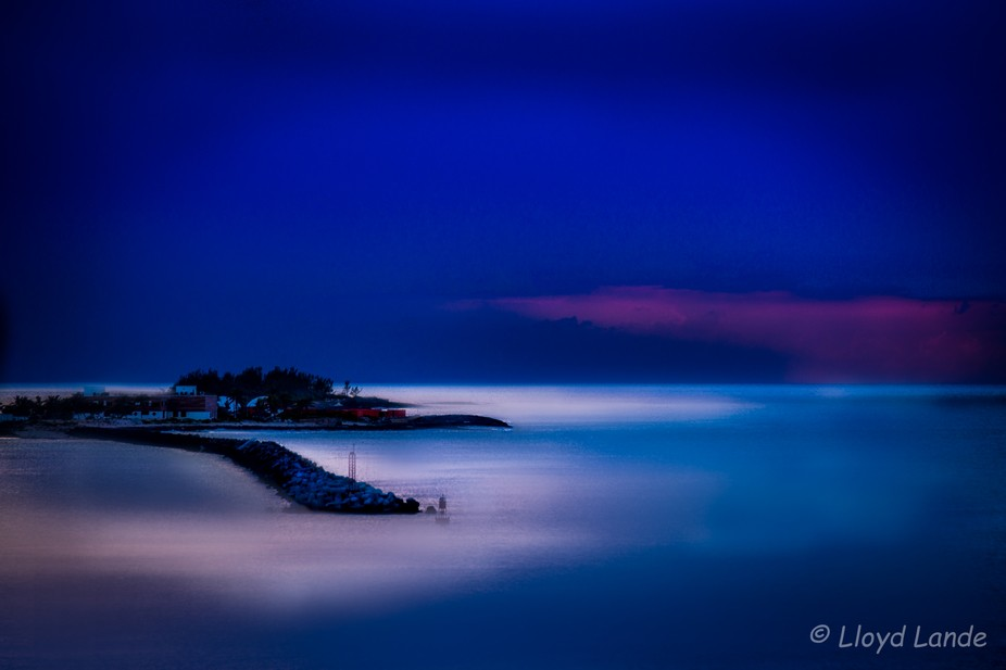 This photo taken from the deck of a cruise ship of a tiny little island in the Bahamas at Dusk, c...
