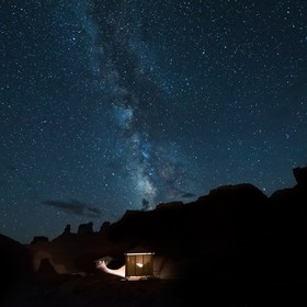 Desert canyons with milky way stars at night and illuminated house in Goblin Valley State Park