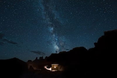 Desert canyons with milky way stars at night and illuminated house
