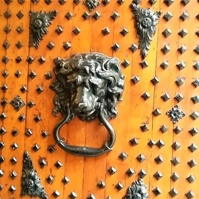 Medieval solid wooden door with a lion's head handle