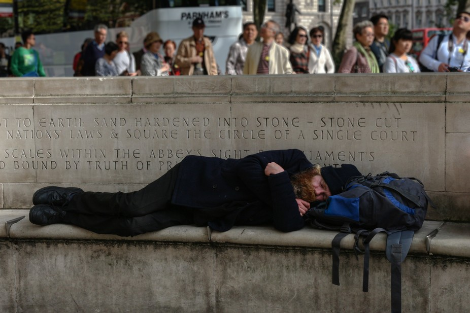 A man laying on a stone bench in the center of London
