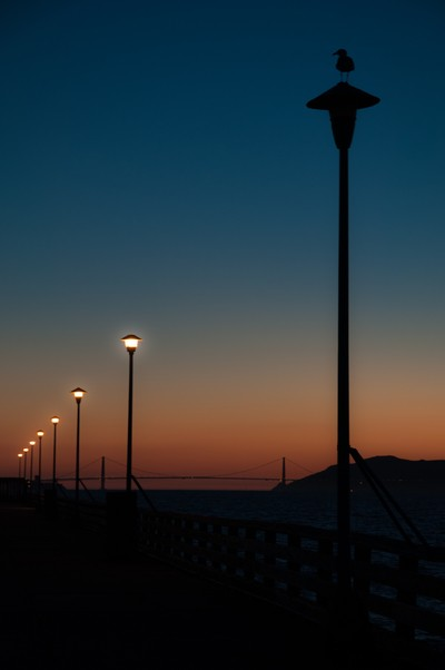 Sunset silhouettes and the Bay Bridge in the distance, Berkeley Pier, USA