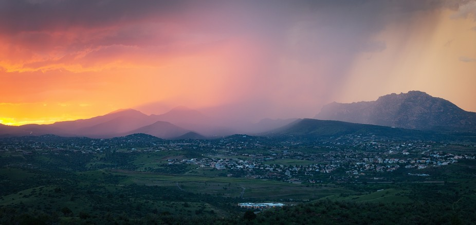 The sun setting amidst rain and fog over Granite Mountain in Prescott, AZ, USA.