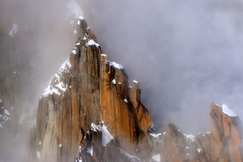 The famous face of the Dru (Chamonix) appears through the mist (taken from a helicopter).