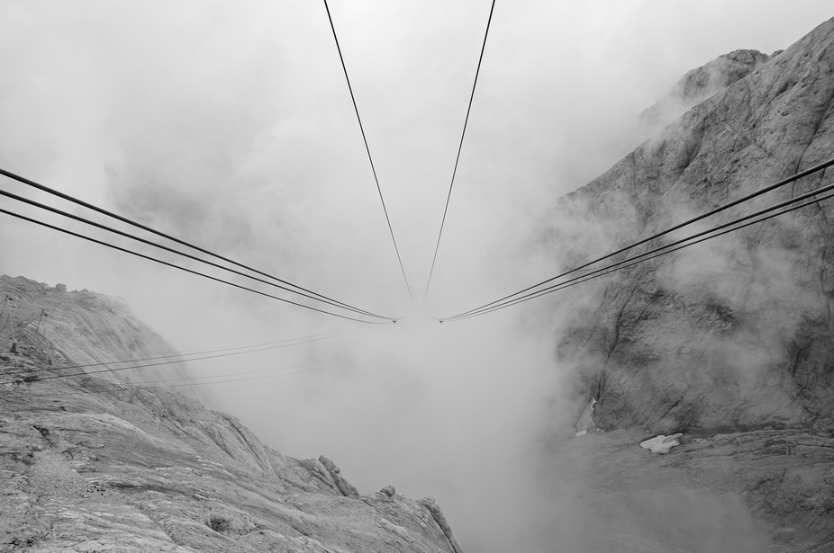 On top of Marmolada glacier, looking down to the base of the ropeway between the clouds.