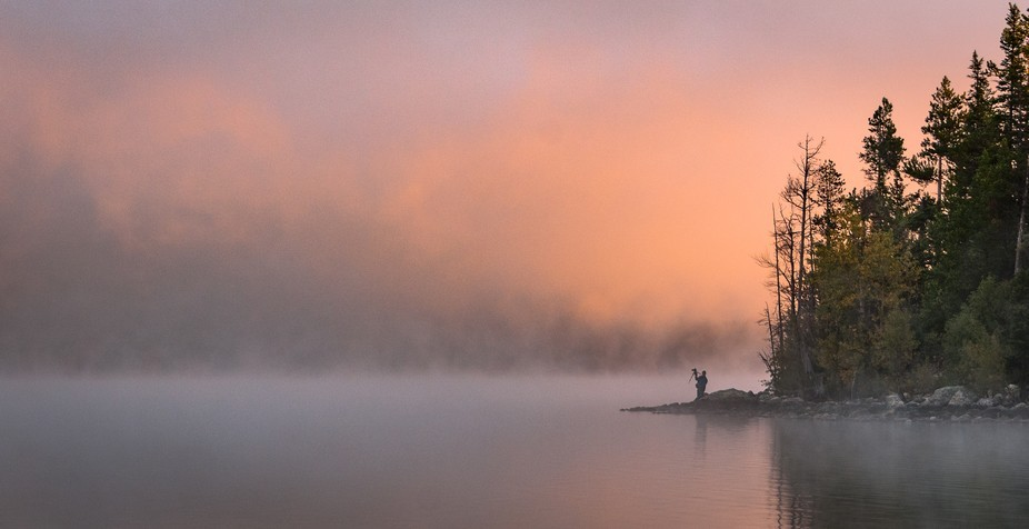 A foggy sunrise on Oxbow Bend in Grand Tetons National Park, and a photographer setting up to tak...