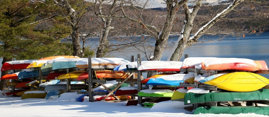 Right after a snowstorm, the sun was shining just right on these kayaks stored for the winter.