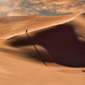 An unusually long shadow follows a hiker as he trudges up a ridge on one of the dunes at Coral Pink Sand Dunes State Park in Utah.