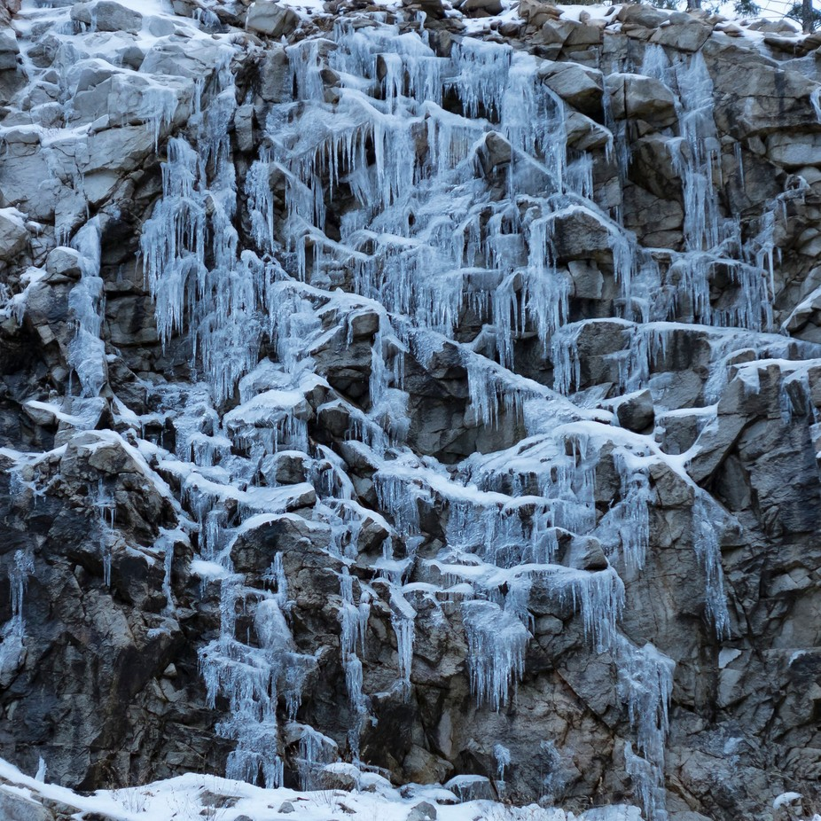 Steep cliff yielding a variety of icicles with an overall hexagonal pattern even in the rock itself.