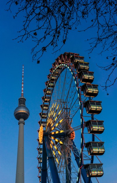 Winter carnival lights with an ornate ferris wheel and the Fernsehturm TV Tower in Berlin, Germany