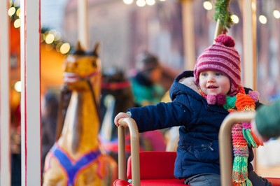 Child on a carousel at a carnival or festival. Decorative ornate horse at a fun fair in Berlin, Germany