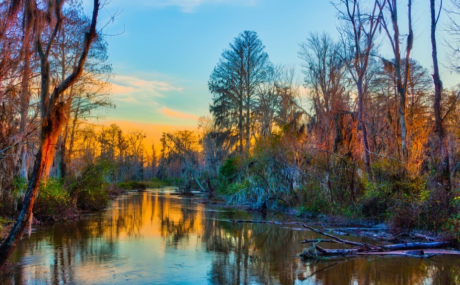 The sky and the trees alongside Butler Creek are bathed in a multitude of colors as the sun sets....