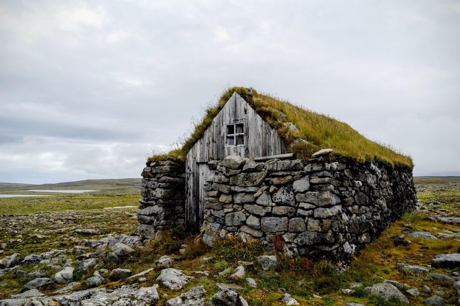 On the top of a rugged mountain, without tree or shrub anywhere nearby, a lonely house stood all ...