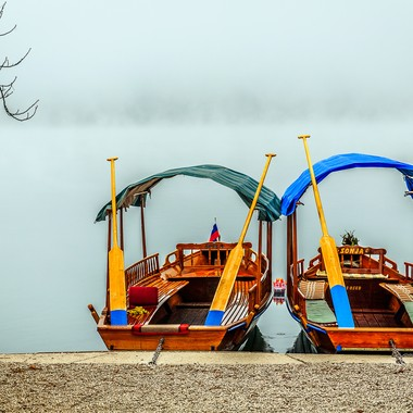 Two boats sitting along the serene banks of Lake Bled in Slovenia in the morning fog.