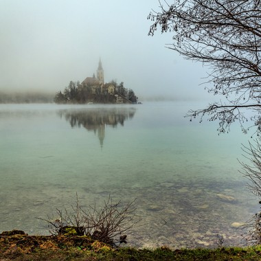 The beautiful greenish blue water of Lake Bled with the island church in the foggy background.