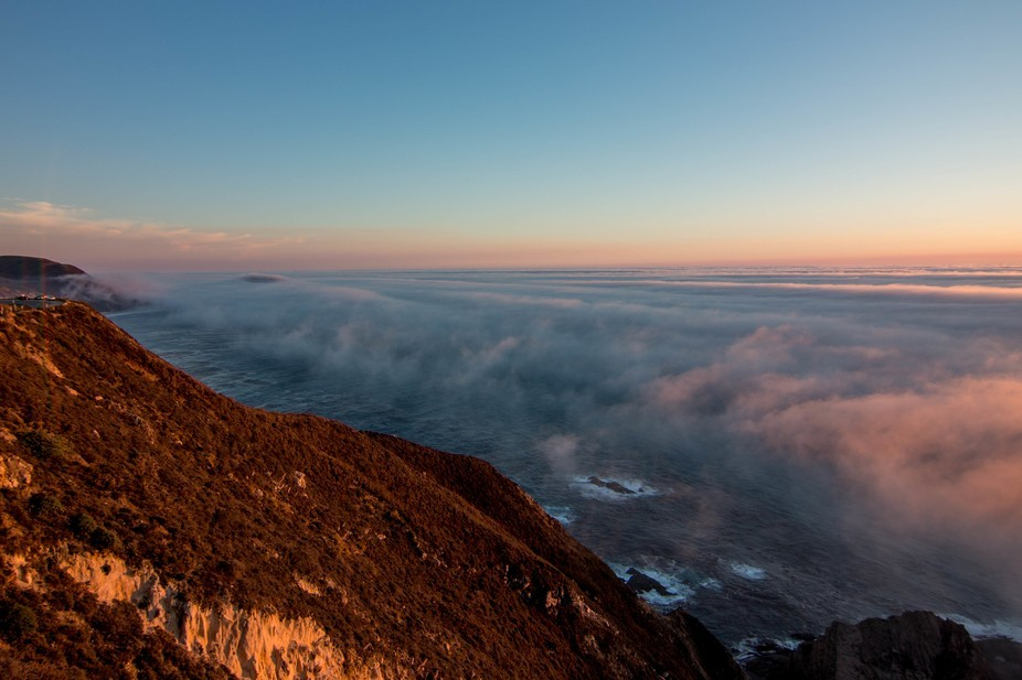 A candid view of our beautiful Big Sur CA coastline as the sunset casts subtle hues across the layers of clouds and down the majestic cliffs