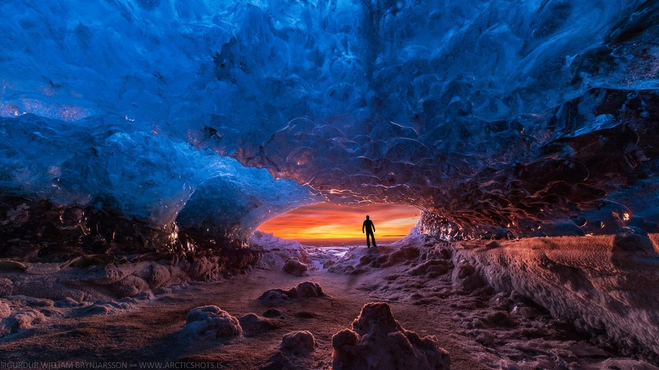 The burning sunrise shone its warm rays into the frozen ice cave in Vatnajokull glacier, creating...