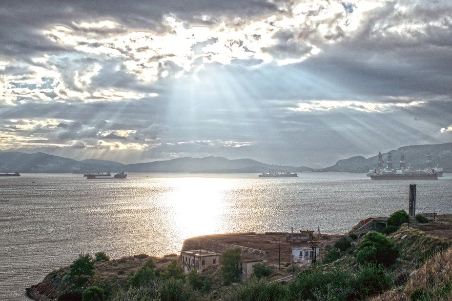 The sun breaking through the morning clouds over the Gulf of Elefsina in Greece.
