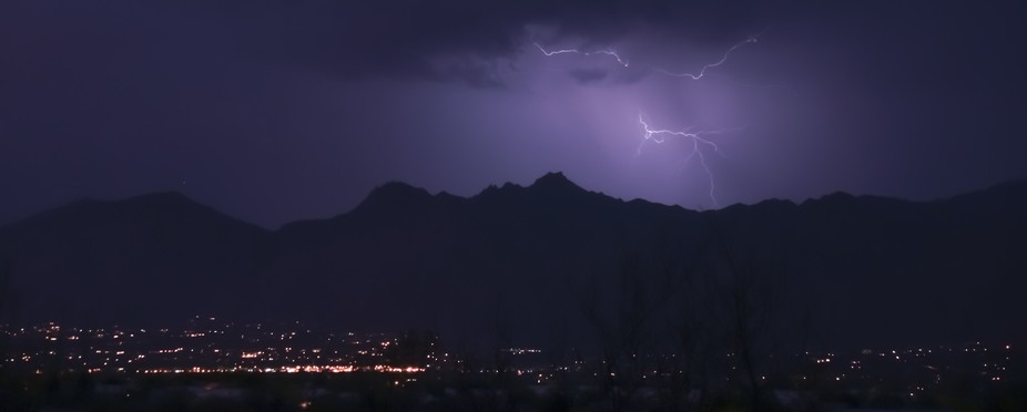 The sky gets painted with streaks of lightning and brings out the mountain silhouettes