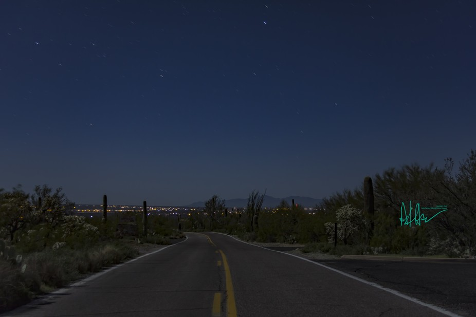 A lonely road to the city on a summer night in the desert.